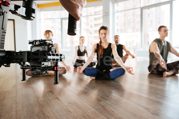 Video shooting of people doing yoga and meditating. Backstage Stock photo © deandrobot