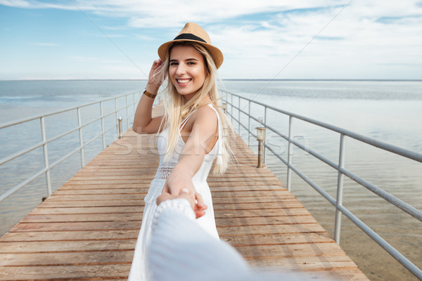 Cheerful woman holding hand and walking with friend on pier Stock photo © deandrobot