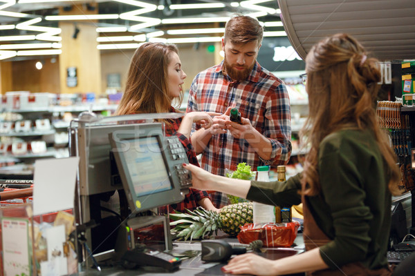 Concentrated young couple standing in supermarket Stock photo © deandrobot