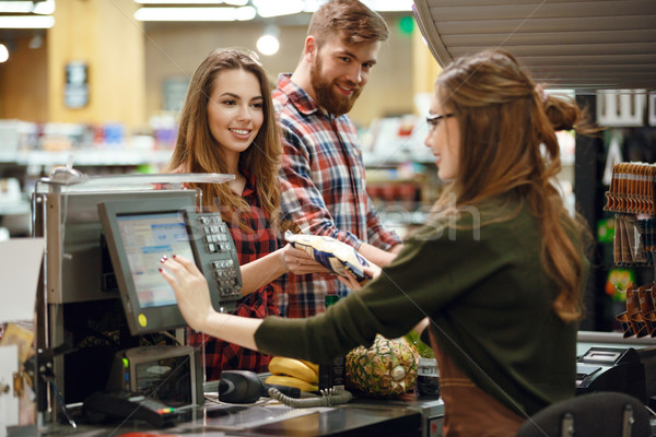 Happy young loving couple standing in supermarket Stock photo © deandrobot