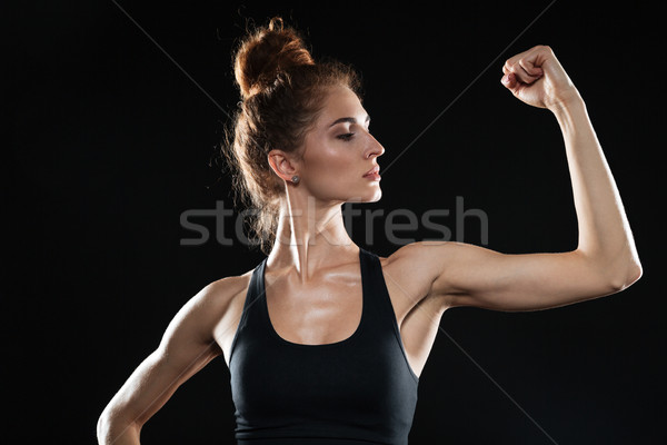 Young sports woman showing her biceps Stock photo © deandrobot