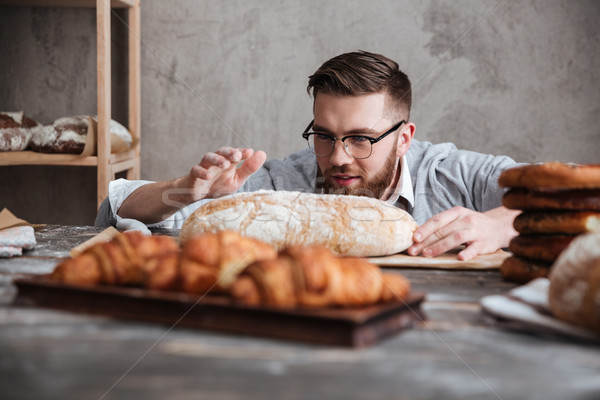 Concentrated man baker standing at bakery near bread. Stock photo © deandrobot