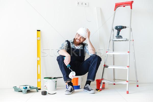 Felice builder seduta secchio guardando fotocamera Foto d'archivio © deandrobot