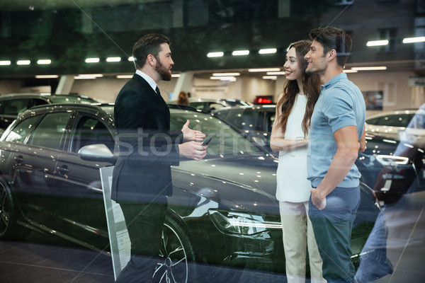 Smiling salesman showing new car to a couple in showroom Stock photo © deandrobot