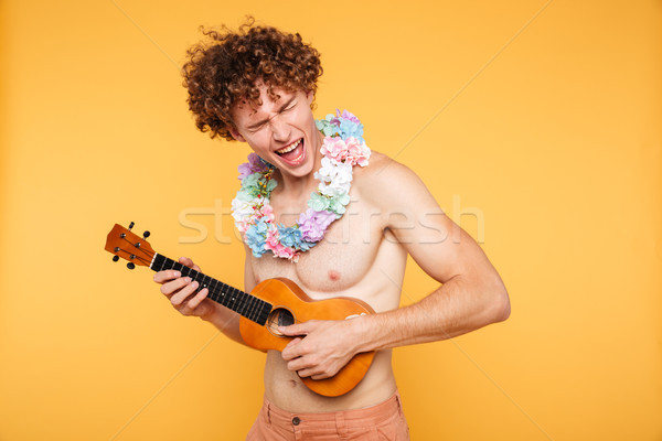 Attractive shirtless man in summer clothes playing ukulele Stock photo © deandrobot