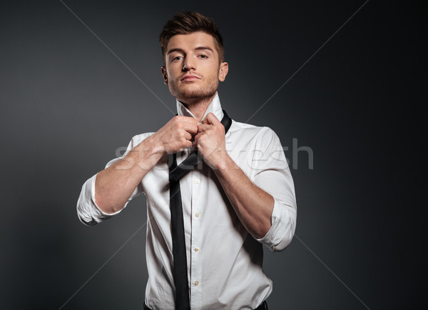 Concentrated young man dressed in formalwear Stock photo © deandrobot