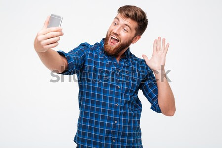Shocked bearded man in checkered shirt writing message on smartphone Stock photo © deandrobot