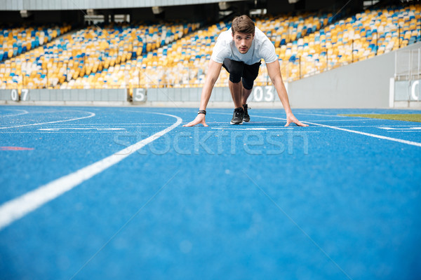 Young male athlete standing in a start position Stock photo © deandrobot