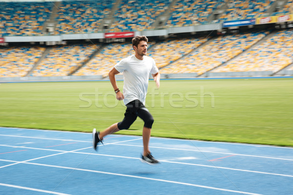 Side view of a young professional sprinter running Stock photo © deandrobot