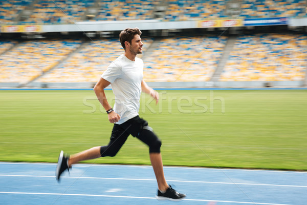 Side view of a young sportsman running on a racetrack Stock photo © deandrobot