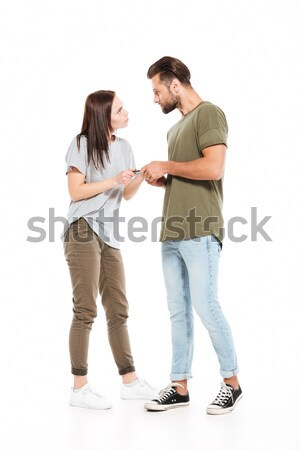 Angry young loving couple holding phone. Stock photo © deandrobot