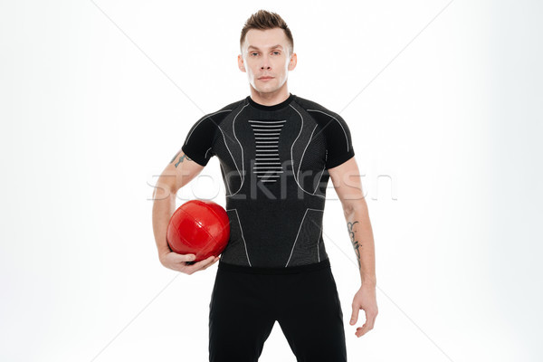 Portrait of a confident healthy sportsman holding red fitness ball Stock photo © deandrobot
