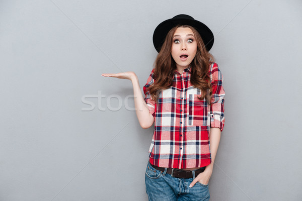 Portrait of a surprised shocked young woman in plaid shirt Stock photo © deandrobot