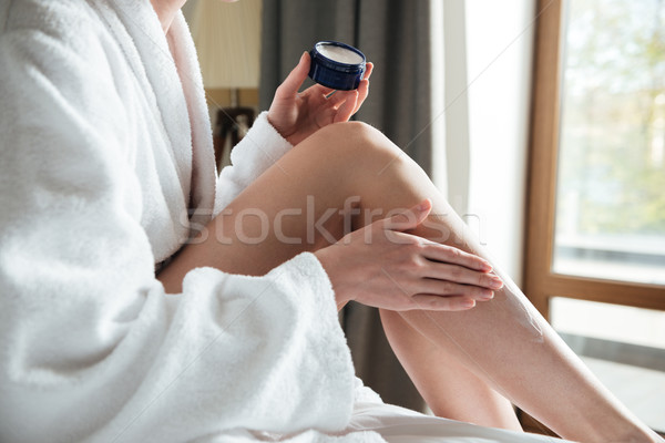 Close up portrait of a woman applying cream on her legs Stock photo © deandrobot