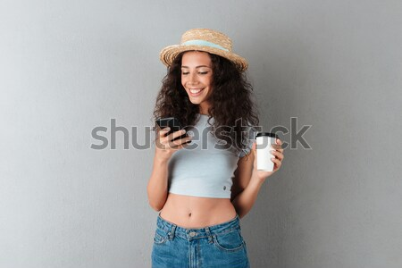 Smiling curly woman drinking coffee and using smartphone Stock photo © deandrobot