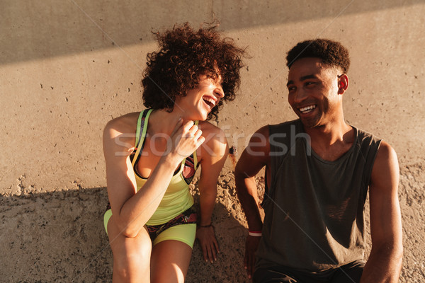 Two happy sports people sitting on pier while having rest Stock photo © deandrobot