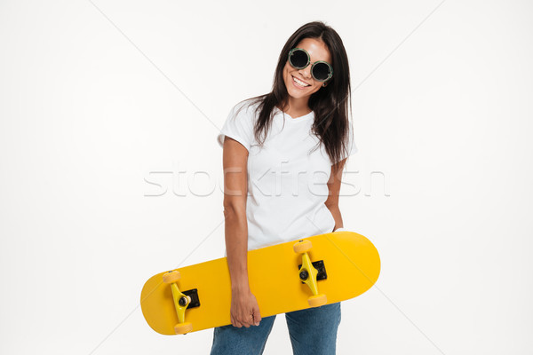 Portrait of a happy cheerful woman holding skateboard Stock photo © deandrobot