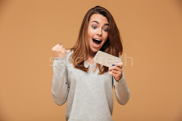 Happy attractive brunette girl joying win in video game on smart Stock photo © deandrobot
