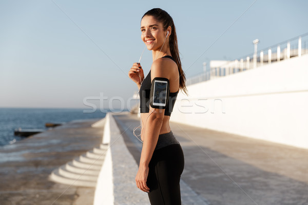 Stock photo: Happy young sports woman listening music outdoors.