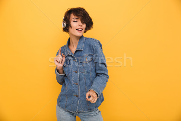 Portrait of a smiling satisfied girl dressed in denim jacket Stock photo © deandrobot