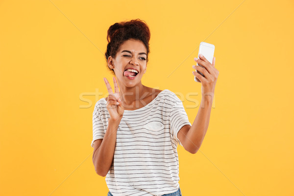 Funny african lady grimacing and making selfie on smartphone isolated Stock photo © deandrobot