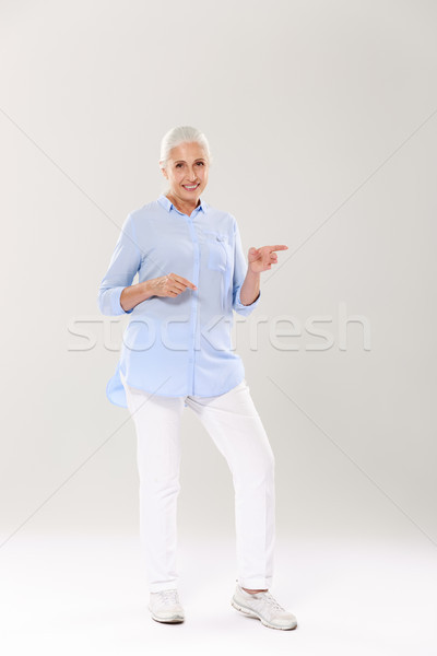Full-length portrait of happy senior  gray-haired woman, standin Stock photo © deandrobot