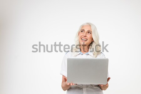 Mature grey-haired woman smiling and showing blank screen of laptop isolated Stock photo © deandrobot