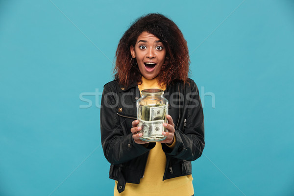 Shocked happy african woman in leather jacket holding jar Stock photo © deandrobot