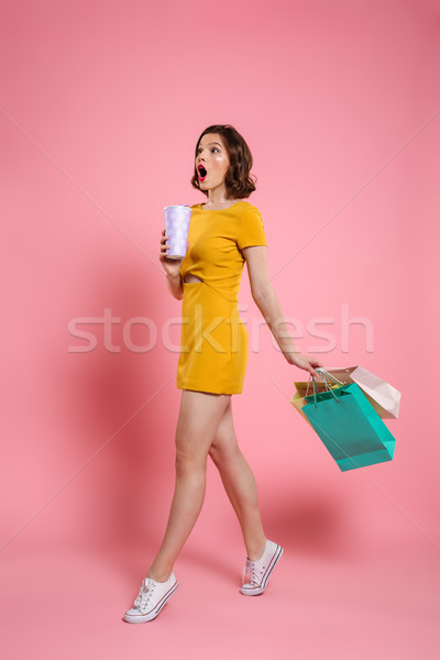 Full length photo of cute amazed woman in yellow dress holding d Stock photo © deandrobot
