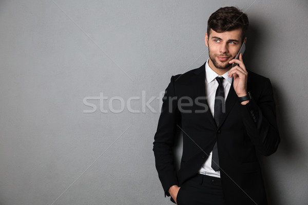 Cheerful bearded guy in black suit speaking on mobile phone, loo Stock photo © deandrobot