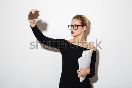 Calm business woman in dress and eyeglasses holding documents Stock photo © deandrobot