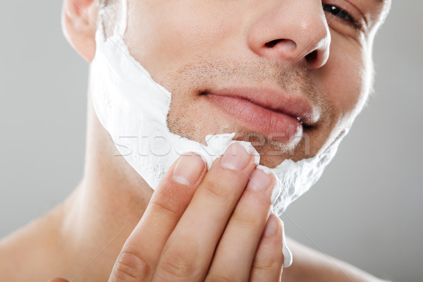 Close up portrait of a happy man applying shaving foam Stock photo © deandrobot