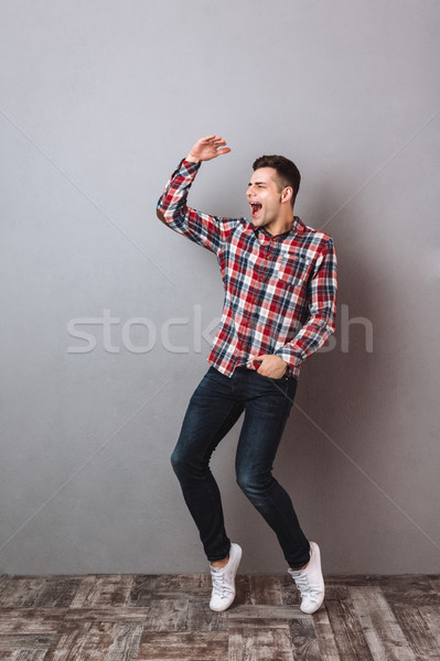 Full-length image of Screaming happy man in shirt and jeans Stock photo © deandrobot
