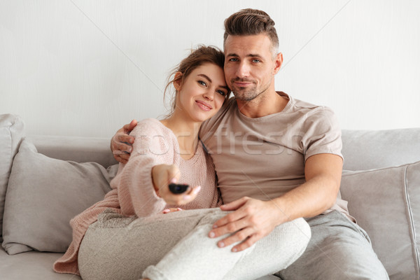 Portrait of an attractive young couple sitting on a couch Stock photo © deandrobot