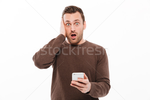 Geschokt jonge man mobiele telefoon afbeelding permanente Stockfoto © deandrobot