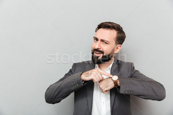Horizontal image of bearded man pointing at his wrist watch, pos Stock photo © deandrobot