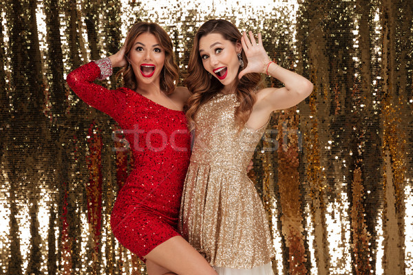 Portrait of two attractive happy women in sparkly dresses Stock photo © deandrobot