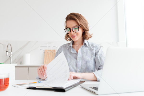 Photo of cheerful attractive woman in glasses reading new contra Stock photo © deandrobot