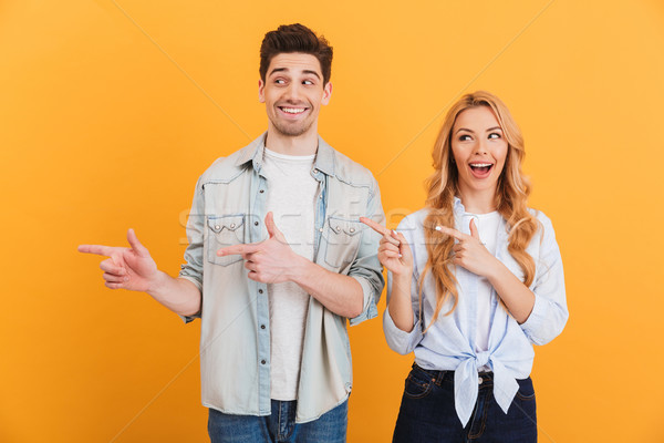 Photo of happy man and woman in basic clothing smiling and point Stock photo © deandrobot
