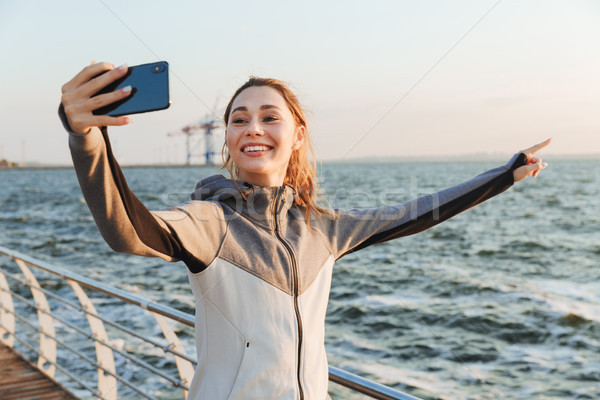 Excited young sportswoman taking selfie with mobile phone Stock photo © deandrobot