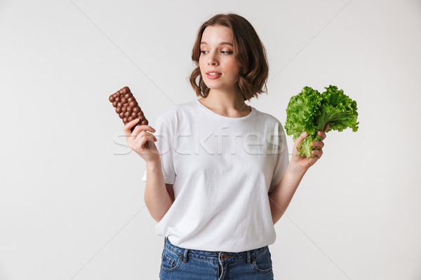Portrait of a confused young woman holding chocolate bar Stock photo © deandrobot