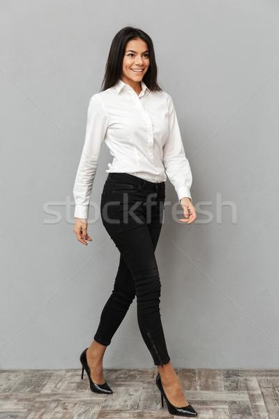 Full length image of smiling businesslike woman in white shirt a Stock photo © deandrobot