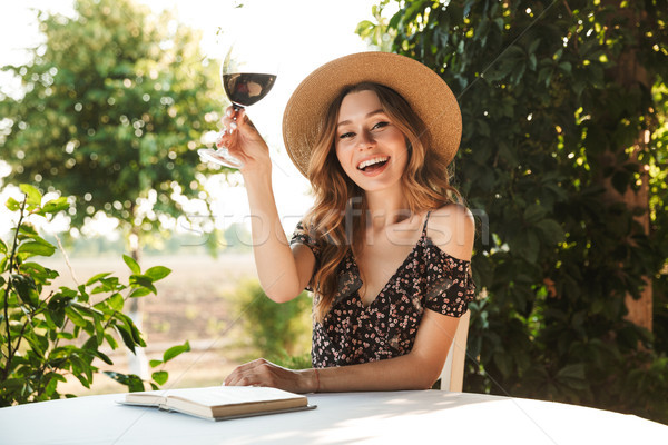 Photo of happy young woman wearing straw hat drinking wine, whil Stock photo © deandrobot