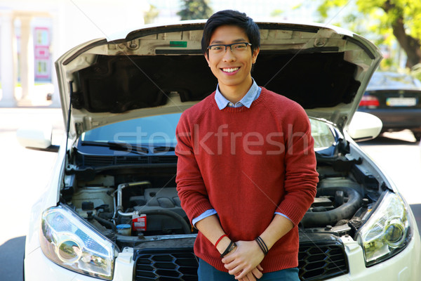 Stock photo: Young asian man standing near car with bonnet open
