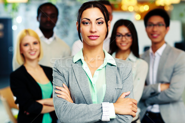 Beautiful businesswoman with arms folded standing in front her colleagues Stock photo © deandrobot