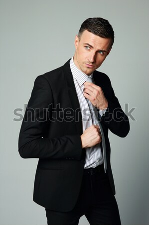 Handsome businessman straightening his tie on gray background Stock photo © deandrobot