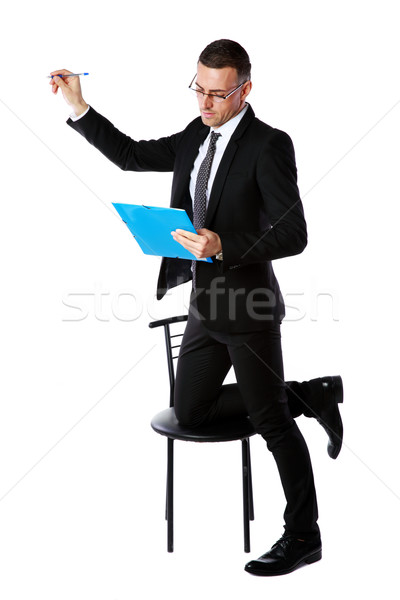 Businessman in glasses writes with pen at copyspace over white background Stock photo © deandrobot