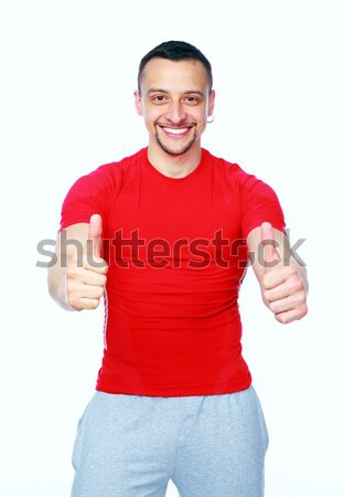Sportive man thumbing up in red T-shirt over white background Stock photo © deandrobot