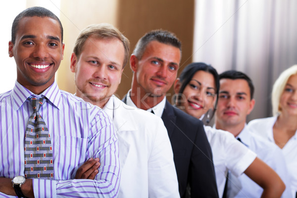 group of business people smiling in an office lined up Stock photo © deandrobot