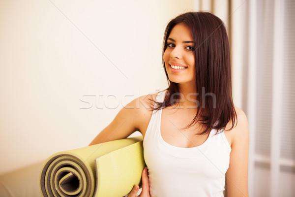 Young happy woman with yoga mat is ready for fitness Stock photo © deandrobot
